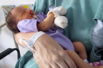 Nina no colo da mamãe na U.C.I.